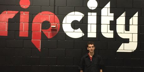 "Josh Maclay standing in front of a black wall with the words ""rip city"" painted in red and white."