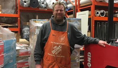 Kevin Moran, standing in front of a forklift and wearing an orange Home Depot apron.