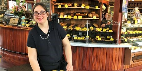 Kristen Cibula, standing in front of a counter with baked goods at a restaurant.