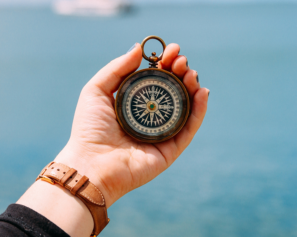 A hand holding a compass, focused, with a out of focus blue background.