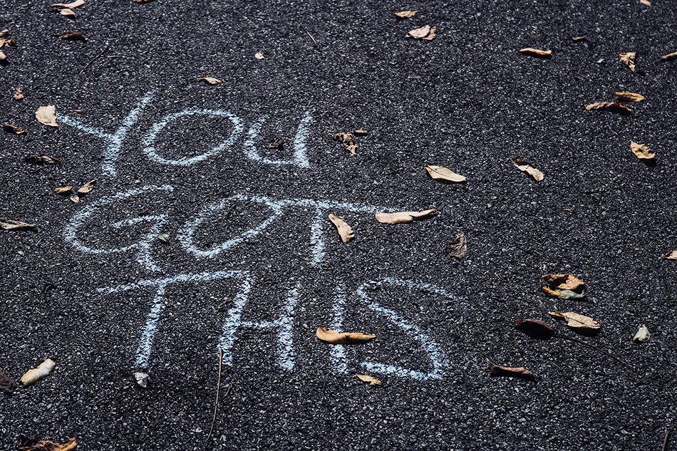 "A close up of cement ground with ""you got this"" written in chalk."