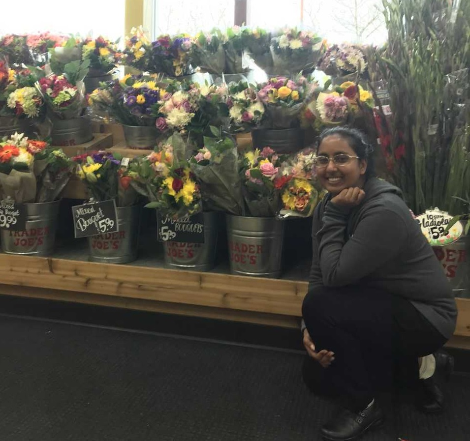 Shaina Leiman kneeling in front of a display of flower bouquets at Trader Joe's.
