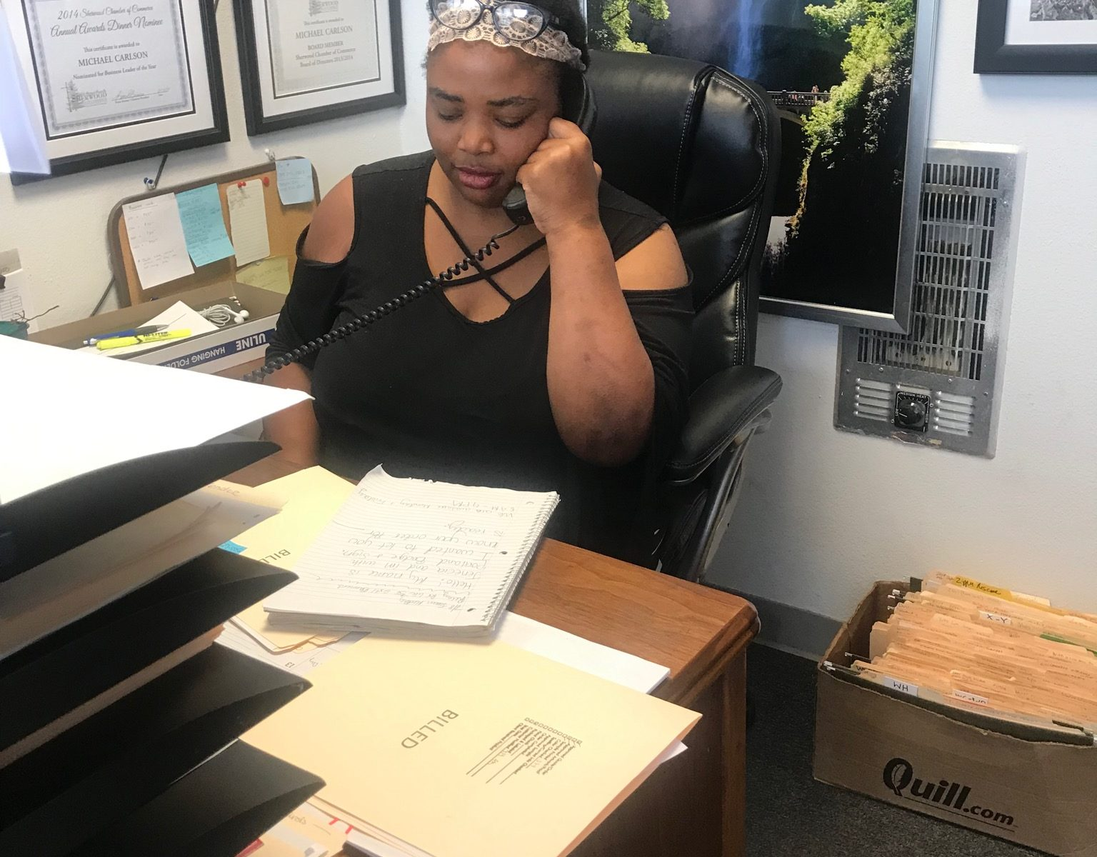 Jenecia Lawson, seated at a desk speaking on a corded phone.